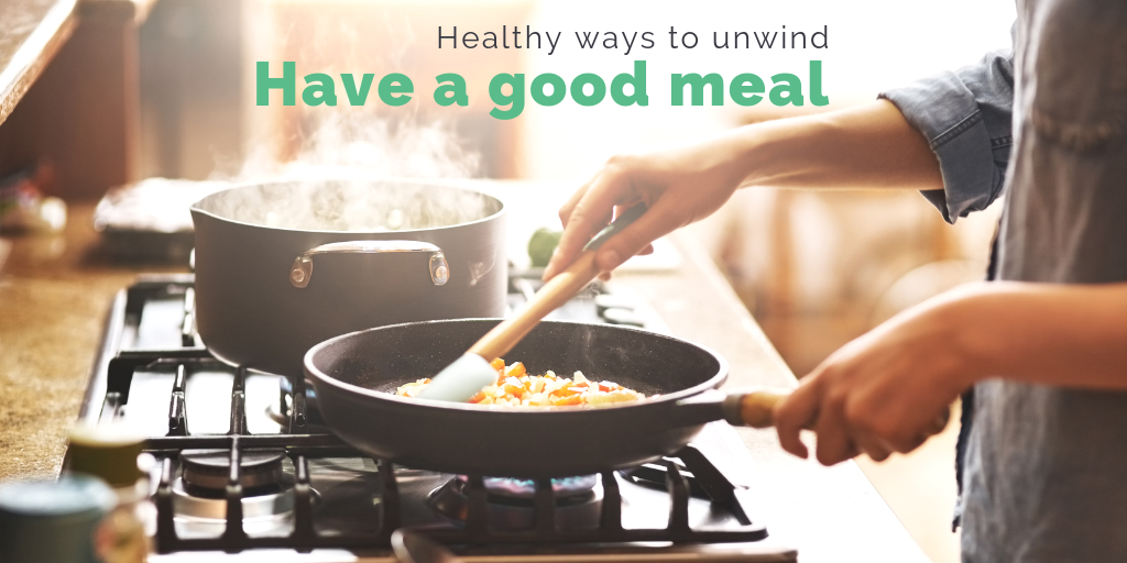 """""""Healthy ways to unwind: Have a good meal"""". Someone tending to a pan on a stove while steam rises from a pot."""