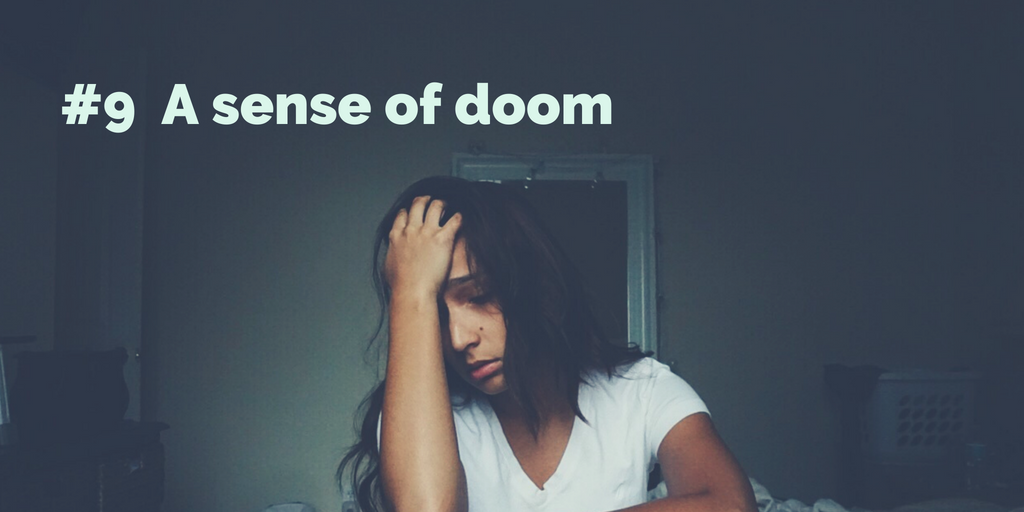 9-A sense of doom. A woman in a dark room with a hand on her forehead, eyes closed in misery.