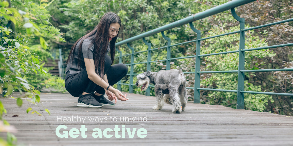 """""""Healthy ways to unwind: Get active"""". A woman plays with her dog."""