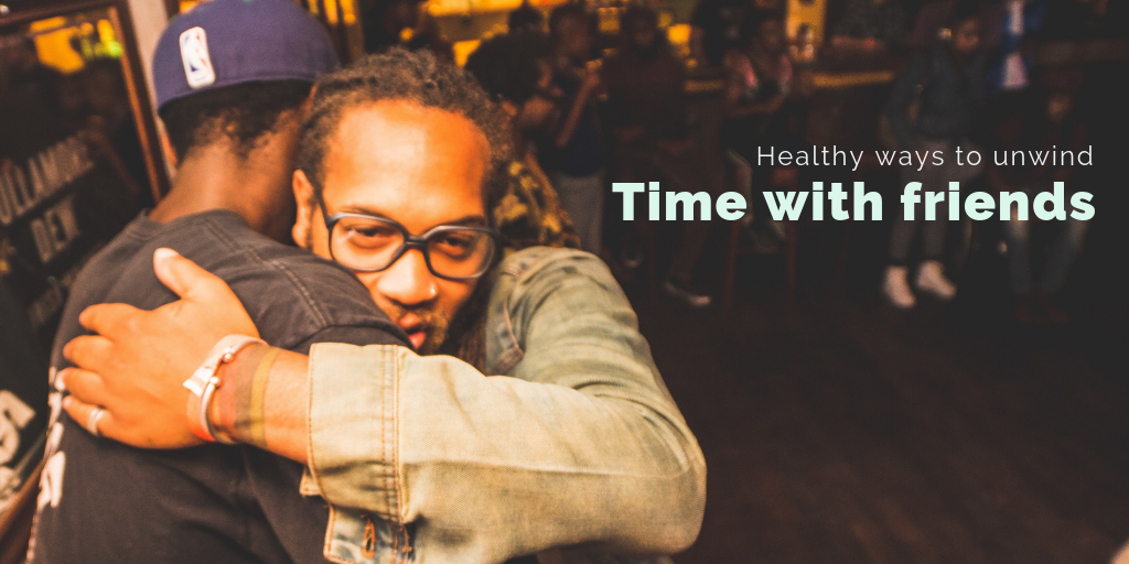 """""""Healthy ways to unwind: Time with friends"""". Two men hug while meeting at a bar."""